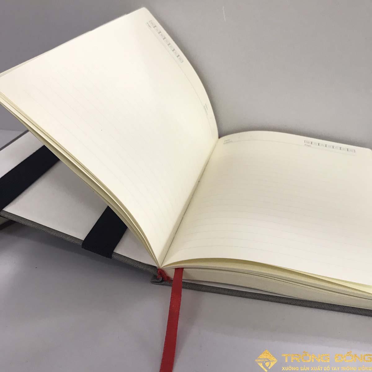 Phần ruột sổ dán gáy, giấy có màu kem và kẻ ngang.